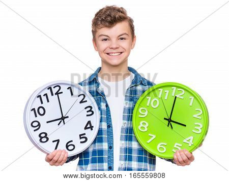 Portrait of caucasian teen boy with clock. Funny teenager showing clock, looking at camera. Child back to school, isolated on white. Education and time concept.