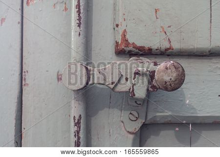 detail old wooden door safety lock, vintage painted covering wood, metal and screws. Timeworn paint