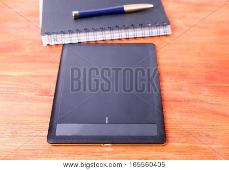 Black tablet pen and diary on a wooden table