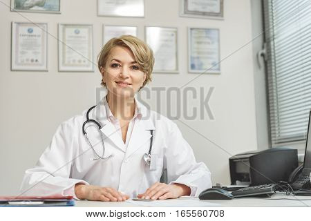 Confident doctor is sitting near desk. She looking at camera with light smile