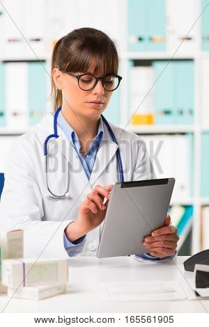 Thoughtful Female Doctor At Desk Using Tablet