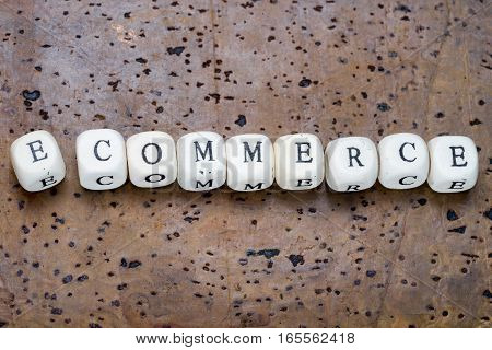 E-commerce text on wooden cubes on a brown cork background