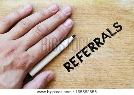 Human hand over wooden background and referrals text concept
