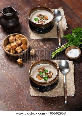 Homemade champignon soup on wooden grunge background.