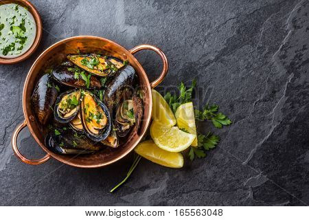 Shellfish Mussels in copper bowl with lemon and herbs. Shellfish seafood. Top view
