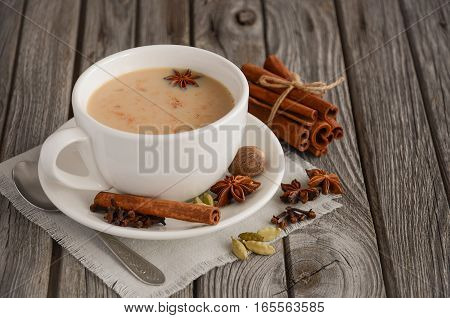 Indian masala chai tea. Spiced tea with milk on the rustic wooden table.