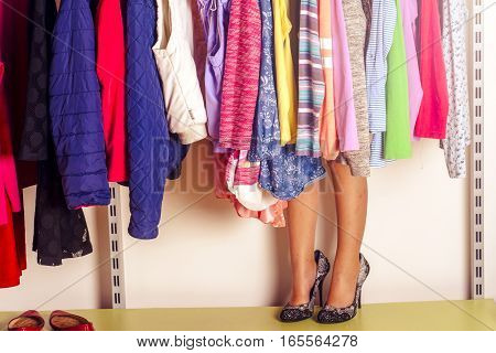 Little girl child choosing clothes to wear in wardrobe. Beautiful legs. Fashion clothing sale concept.