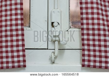Old wooden window lock, painted covering wood, metal and screws. With Vintage curtain with grid pattern