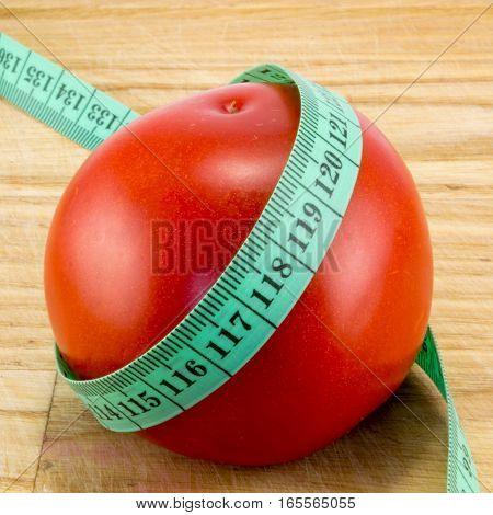 A diet using red tomatoes concept using centimeter to measure the calories