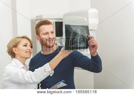 Doctor is standing nearby male patient. They looking at radiograph of man with smile