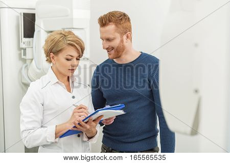 Concentrated physician is standing beside happy patient. He looking at medico with smile