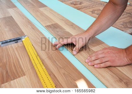 Contractor laying laminate flooring. Installing wooden laminate flooring. Step by Step.
