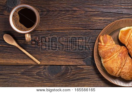 Cup of hot coffee and croissant on wooden background top view. Space for text