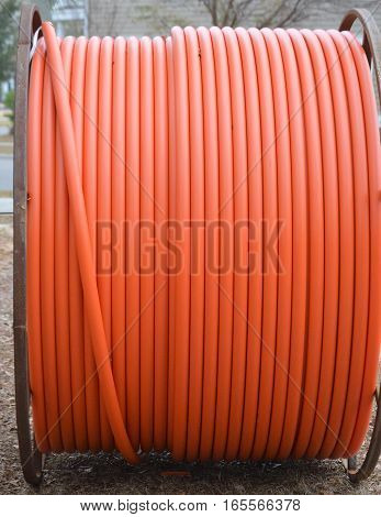 orange fiber optic cable on metal spool