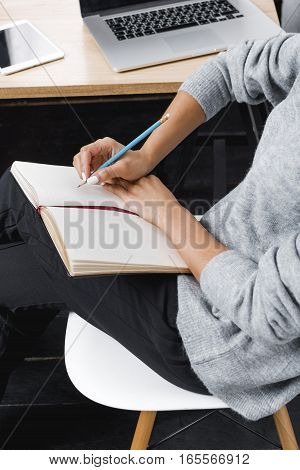 Businesswoman sitting at table with laptop, taking notes