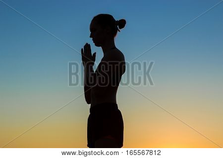 Sporty woman practicing yoga in the park at sunset - making hand greeting namaste. Sunset light, golden hour, lens flares. Freedom, health and yoga concept
