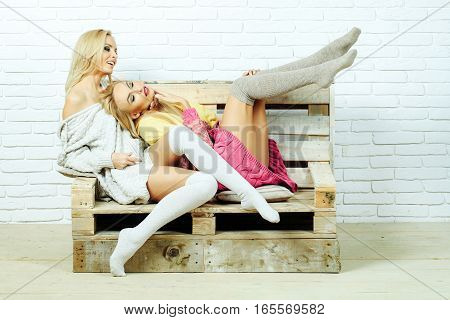 Pretty smiling girls or two sexy cute women with blond hair in home sweaters and socks sit on wooden pallet sofa on white brick wall