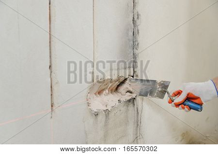 Installing electrical socket box. A worker puts plaster into the hole on the wall to install socket box.