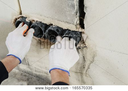 Installing electrical socket box. A worker attaches to the wall socket box using gypsum plaster.