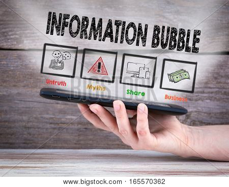 Information Bubble. Tablet computer in the hand. Old wooden background.