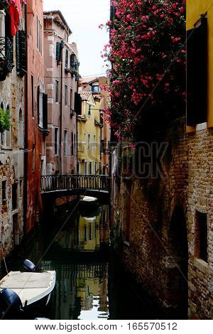 Beautiful colorful street with flowers canal and boat in Venice Italy