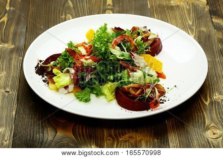 Delicious vegetable salad mixed with mushrooms greens red beet orange sweet pepper sprouts onion on plate on wooden background. Modern molecular gastronomy