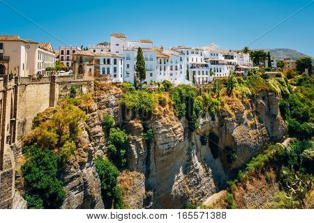 White Traditional Houses Over The Tajo De Ronda Is A Gorge Carved By The Guadalevin River, On Which The Town Of Ronda, Spain.
