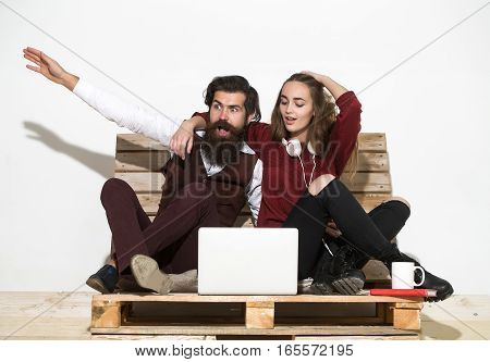 Shocked young couple use laptop. Disappointed pretty girl or beautiful woman and handsome man bearded hipster with beard shout on wooden pallet sofa.