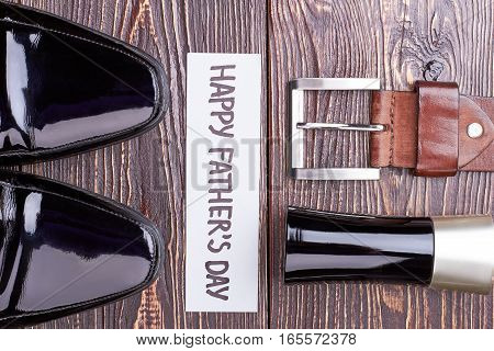 Black shoes near greeting card. Belt on wooden background. Change your look with accessories.