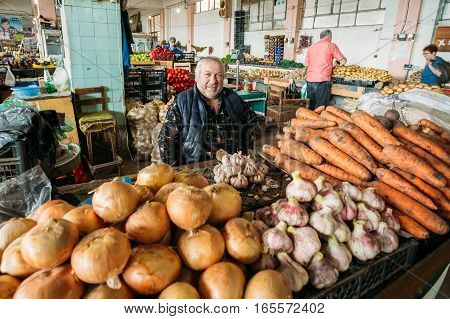 Batumi, Georgia - May 28, 2016: The Mature Stocky Georgian Man, The Dealer  Of Vegetables Is Sitting At The Counter At Covered Market Bazar.