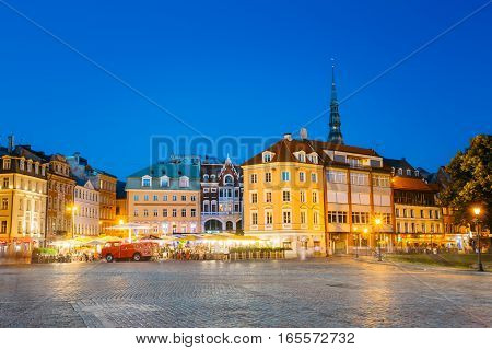 Riga, Latvia - July 1, 2016: View Of Ancient Architectural Buildings Of Old Town On Dome Square In Bright Evening Illumination, Popular Touristic Showplace With Outdoor Cafe In Summer Under Blue Sky.