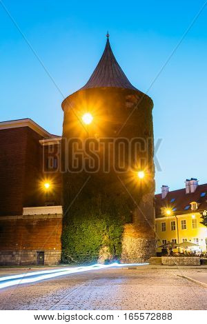 Riga Latvia. View Of Powder Tower On Smilsu Street, Only Extant Construction Of Ancient Fortification System Of Old Town In Evening Lights Under Summer Blue Sky. Motion Blur Effect On Cobbled Road