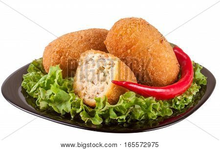 three fried breaded cutlet with lettuce on a black plate isolated white background.