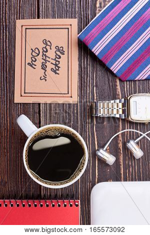 Coffee cup and greeting card. Notepad and earphones on wood. Start your day with coffee.