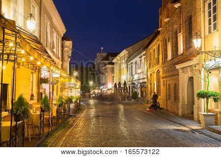 Vilnius, Lithuania - July 8, 2016: Brightly Illuminated Pilies Street Of Old Town, Ancient Architecture And  Deserted Cozy Outdoor Cafes, Popular Showplace Under Summer Night Blue Sky.