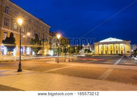 Vilnius, Lithuania. View Of Didzioji Street In Old Town In Bright Evening Illumination With Motion Blur Effect On Road. White City Council Administrative Building Behind, Summer Night, Blue Sky.