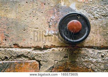 Old vintage door bell button on grunge brick wall