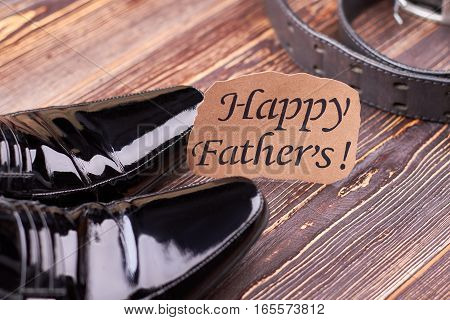 Black footwear and leather belt. Father's Day card on wood. Fashionable look in two steps.