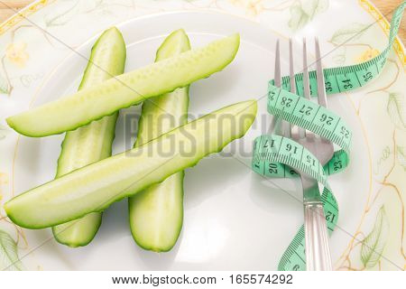cucumber with tape measure isolated on white background