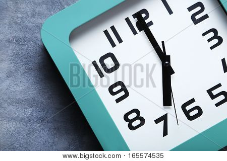 Green clock on a grey wooden table, close up