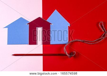 House and house and red carnations on bright colorful background. Home construction concept . Copy space for text.