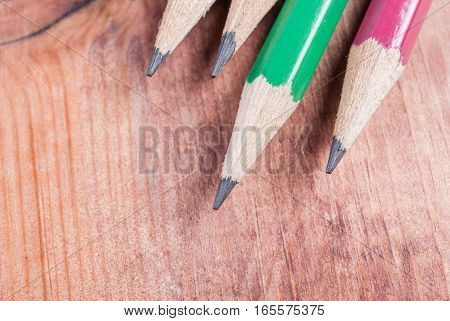 sharpened pencils lying on a wooden surface closeup