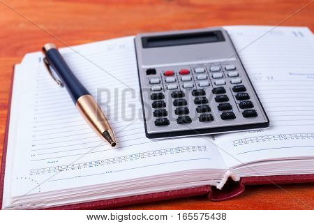Calculator and pen lie on open diary. Business concept