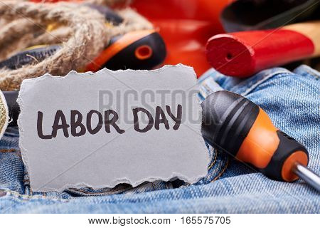 Labor Day card near screwdriver. Rope and screwdriver on jeans. Employment as part of society.