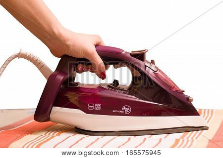 Steam iron in a female hand isolated on white background, ironing towels.
