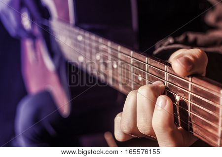 Guitarist with red guitar. The hands on the strings of a guitar fretboard. Accord on a musical instrument.