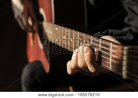 Guitarist with red guitar. The hands on the strings of a guitar fretboard. Accord on a musical instrument. Shallow depth of field.