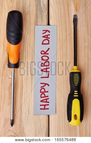 Labour Day card between screwdrivers. Greeting paper and tools. Celebration of workers rights.
