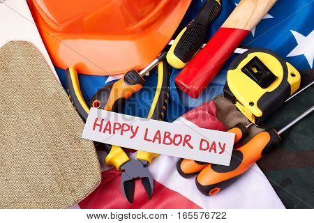 Labour Day card on flag. Tool kit and greeting paper. Labor moves the progress.