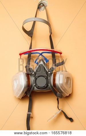 Mask respirator and goggles on the wall. Copy space